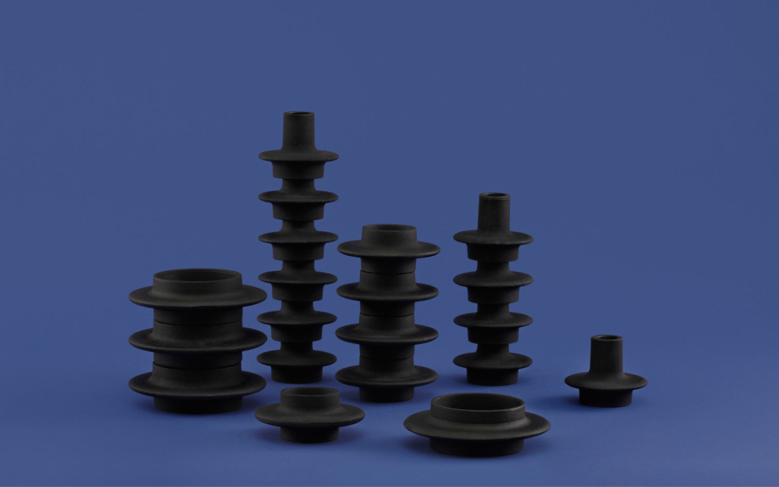 Heima candleholders castiron black familiy stacked group on blue background