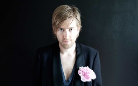 Rasmus gottliebsen on black background black suit with pink flower